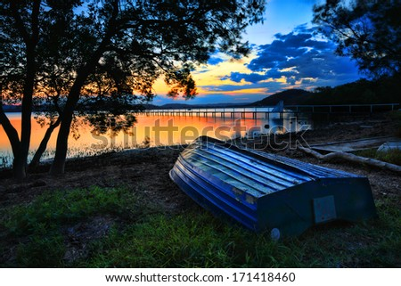 Beautiful sunset landscape with  blue weathered upturned boat at shoreline at low tide.  This pretty spot is Kincumber, Australia.  Please note long exposure, t some motion in trees due to breeze - stock photo