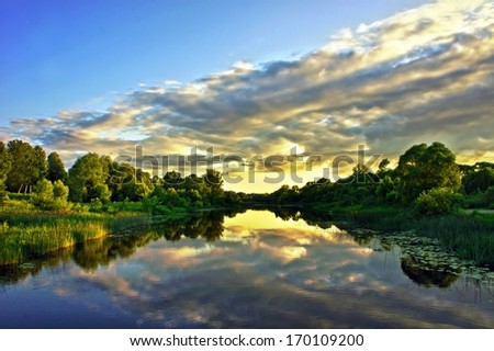 Beautiful Sunset Landscape with reflection on River Sky and Clouds - stock photo