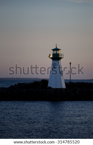 Beautiful sunset light behind a lighthouse on the St. Lawrence river. - stock photo