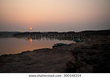 Beautiful sunset Longtail boat, Berth at sand Sam Pan Bok Grand Canyon in Maekhong river, Northeast of Thailand - stock photo