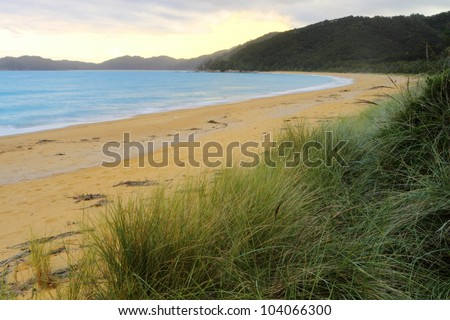 Beautiful sunset on sandy beach of Abel Tasman National Park, South Island, New Zealand - stock photo