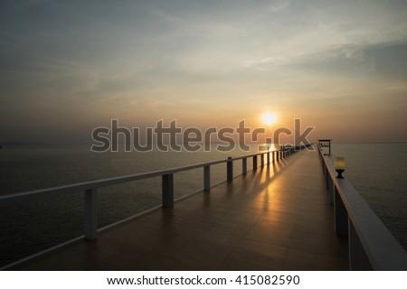 Beautiful sunset on Thailand beach and bridge in silhouette twilight golden hour - stock photo