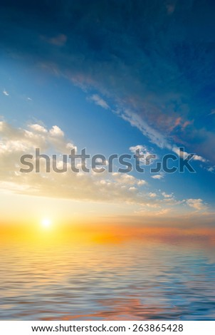 Beautiful sunset on the background of the calm sea and clouds. natural composition