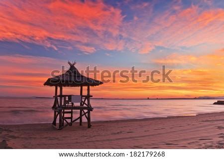 Beautiful sunset on the beach and lifeguard station - stock photo