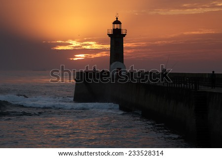 Beautiful sunset on the old pier and lighthouse at the mouth of the river Douro, Porto, Portugal
