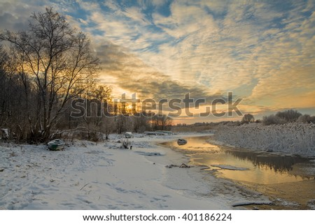 Beautiful Sunset on the river bank in the winter. The boat at the winter river
