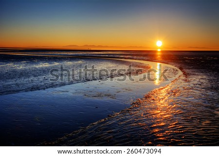 Beautiful sunset over a curving river - stock photo