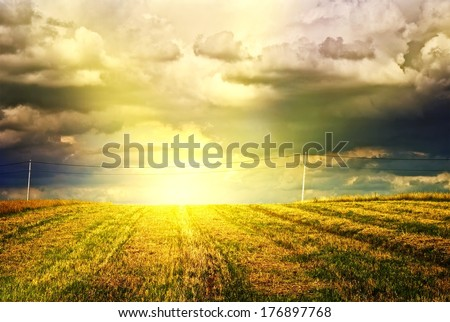 Beautiful sunset over farm field - stock photo
