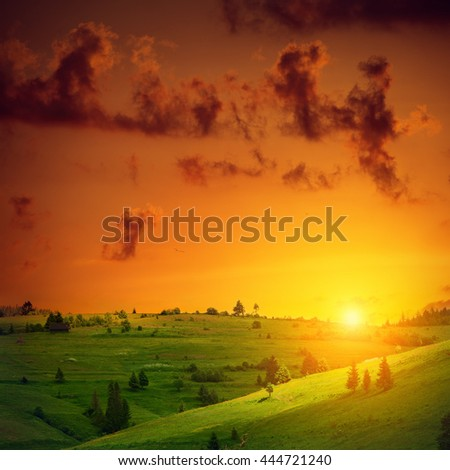 Beautiful sunset over green hill. Rural landscape in summer season