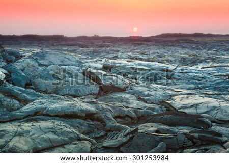 Beautiful sunset over molten cooled lava landscape in Hawaii Volcanoes National Park, Big Island, Hawaii - stock photo