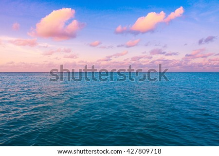 Beautiful sunset over ocean with majestic clouds in the sky - stock photo