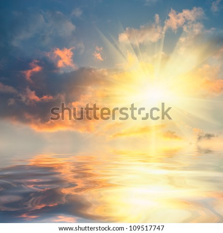 Beautiful sunset over sea with reflection in water, colorful clouds in the sky