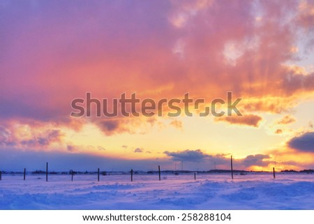 Beautiful sunset over snow on cold and windy winter day - stock photo