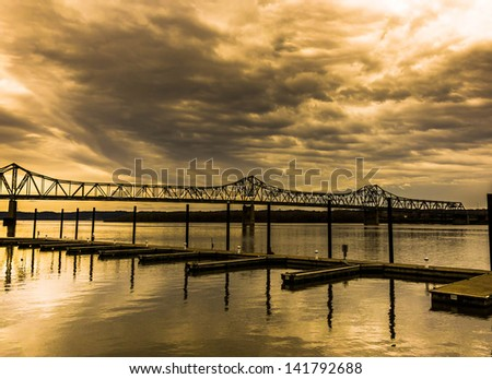 Beautiful sunset over the delicate silhouette of a bridge bridge and boat jetty pier as viewed from riverfront shore