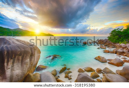 Beautiful sunset over the famous beach Anse Lazio seen from the granite boulders, Praslin island, Seychelles.  - stock photo