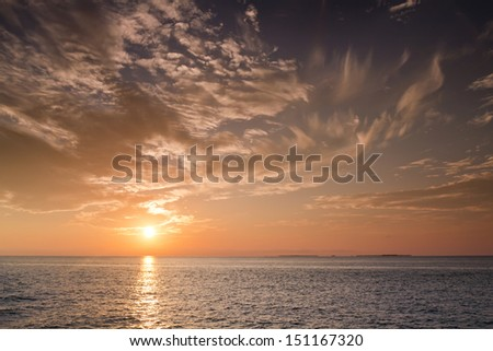 Beautiful Sunset over the ocean waters and Gulf of Mexico in Key West Florida shot during a Sunset Cruise. - stock photo