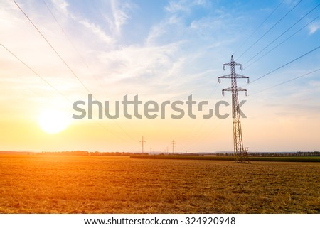 Beautiful sunset over the powerlines on the field - stock photo