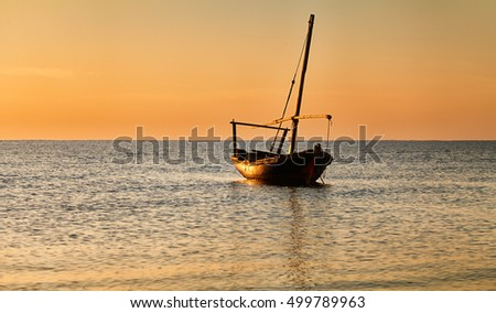 Beautiful sunset over the sea. A small fishing boat in the foreground