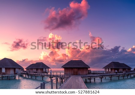 Beautiful sunset over the sea on a cloudy day in Maldives.