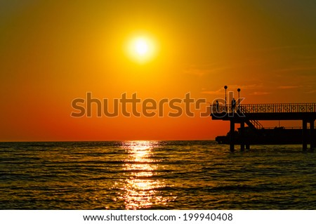 Beautiful sunset over the  sea with seagull on foreground and people silhouettes on pier