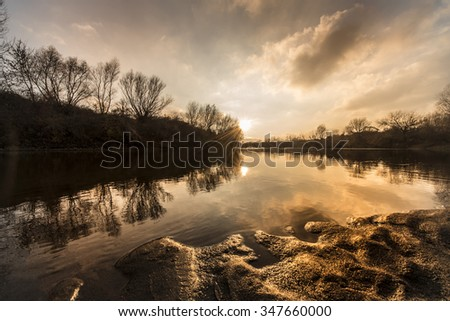 Beautiful sunset over wild river in winter - stock photo