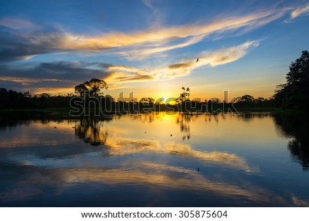 Beautiful sunset reflected on the Yanayacu River in the Amazon rain forest in Peru - stock photo