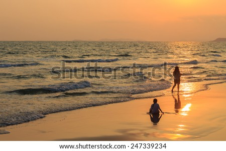 Beautiful sunset scene at sea with little girls - stock photo