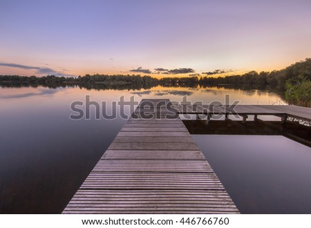 Beautiful sunset seen from a pier in a quiet lake in the city of Groningen, Netherlands - stock photo