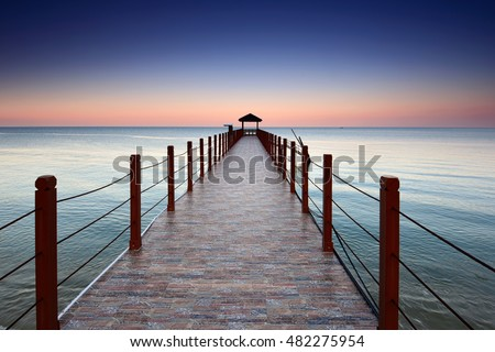 Beautiful sunset view at Kerachut Beach Jetty, Penang National Park during sunset. Soft focus due to long exposure shot. Nature composition.
