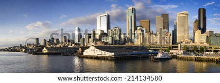 Beautiful sunset view of Seattle Washington's Skyline facing Elliott Bay from downtown to The Seattle Great Wheel. Photo taken from the Bainbridge Island Ferry Terminal. - stock photo