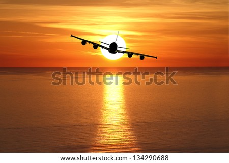 Beautiful sunset with airplane over the sea - stock photo