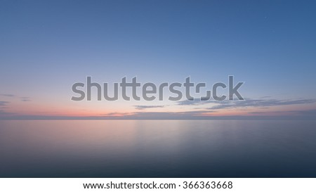 Beautiful sunset with blue sea and sky peaceful background long exposure - stock photo