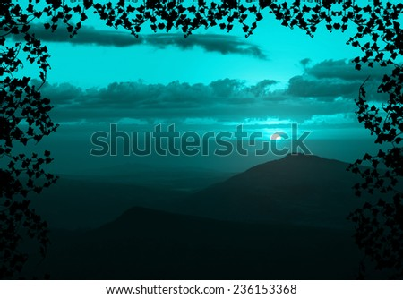 Beautiful sunset with cloud and mountain,tree foreground siluette frame,cyan color tone - stock photo