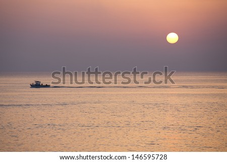 beautiful sunset with fishing boat - stock photo