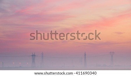 beautiful sunset with high voltage pylons in countryside - stock photo