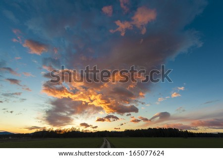Beautiful sunset with meadow and dirt road. - stock photo