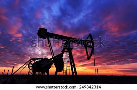 Beautiful sunset with profiled operating gas and oil well pump - stock photo