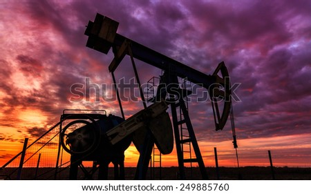 Beautiful sunset with profiled operating gas and oil well pump