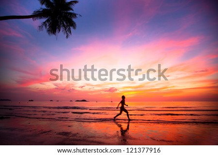 Beautiful sunset with silhouettes of girls on a beach jogger