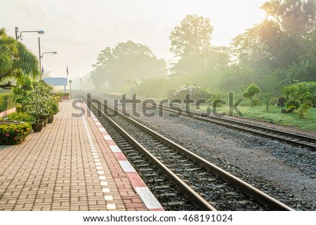 Beautiful sunshine foggy morning at platform of local Thailand train station. Text space.