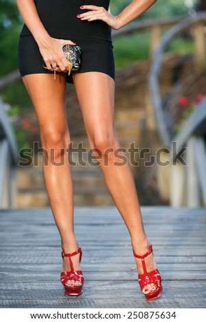beautiful suntanned legs of woman in red strappy heels - stock photo