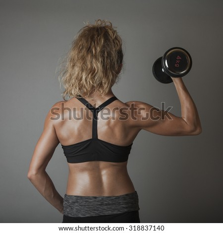 Beautiful super fit young woman showing off her perfect muscular body. Fitness model training with dumbbell (weight) . Perfect Slim Body with sturdy back muscles. Studio shot - stock photo