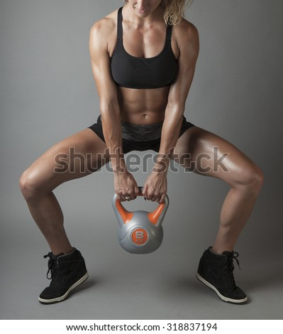 Beautiful super fit young woman showing off her perfect muscular body. Fitness model training with dumbbell (ball weight). Perfect Slim Body. Studio shot - stock photo