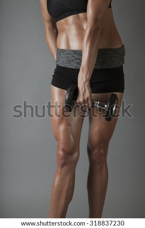 Beautiful super fit young woman showing off her perfect muscular body. Fitness model training with dumbbell (weight) . Perfect Slim Body. Studio shot - stock photo