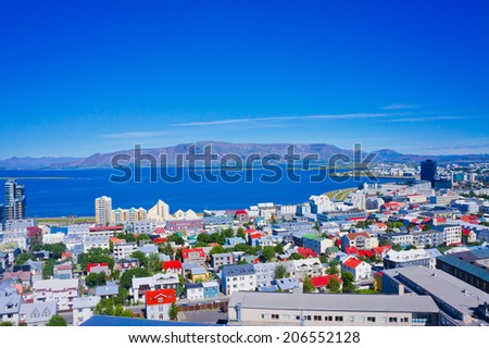 Beautiful super wide-angle aerial view of Reykjavik, Iceland with harbor and skyline mountains and scenery beyond the city, seen from the observation tower of Hallgrimskirkja Cathedral,