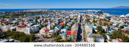 Beautiful super wide-angle aerial view of Reykjavik, Iceland with harbor and skyline mountains and scenery beyond the city, seen from the observation tower of hallgrimskirja  - stock photo