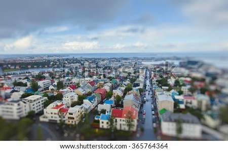 Beautiful super wide-angle aerial view of Reykjavik, Iceland with harbor and skyline mountains and scenery beyond the city, seen from the observation tower of Hallgrimskirkja Cathedral. - stock photo