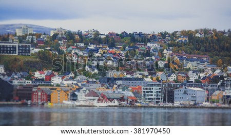 Beautiful super wide-angle panoramic aerial view of Tromso, Norway with harbor and skyline with scenery beyond the city, sunny summer day with blue sky  - stock photo