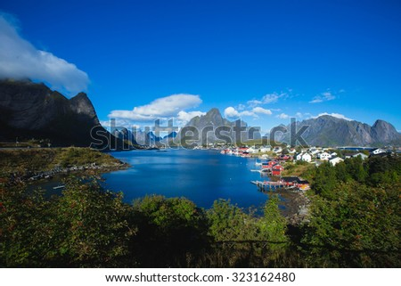 Beautiful super wide-angle summer aerial view of Reine, Norway, Lofoten Islands, with skyline, mountains, famous fishing village with red fishing cabins, Moskenesoya, Nordland - stock photo