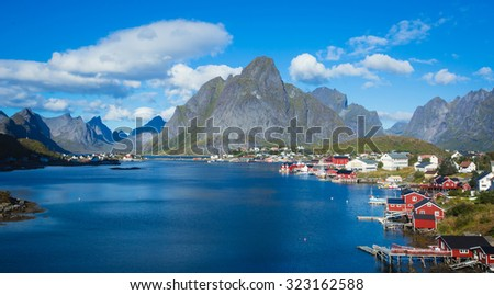 Beautiful super wide-angle summer aerial view of Reine, Norway, Lofoten Islands, with skyline, mountains, famous fishing village with red fishing cabins, Moskenesoya, Nordland